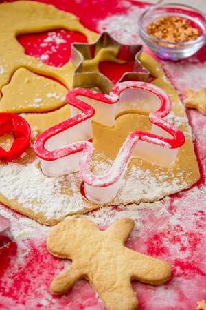 pastry cutters: Cooking gingerbread on the red mat in process . Christmas cookies. Vertical