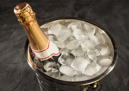 gold capped: Bottle of Champagne in bucket with ice on black background