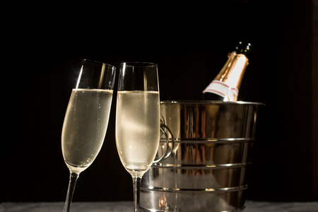 silver bars: Champagne bottle in cooler and two champagne glasses on dark background