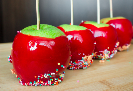 candy apples with confectionery on wooden table