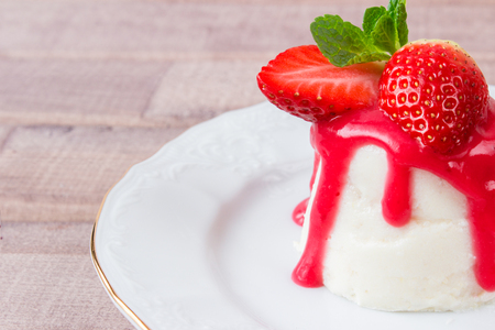 panna cotta dessert with strawberry sirup and mint leaf on light wooden background Stock Photo