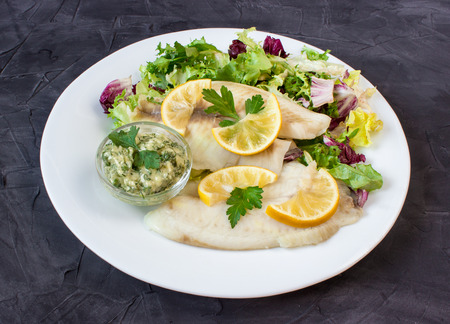 white nile: steamed tilapia fish with salad and tartar sauce on dark background Stock Photo