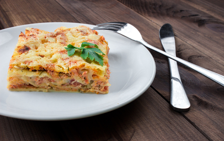 Close-up of a traditional lasagna topped with parskey leafs served on a white plate on dark wooden table Stock Photo