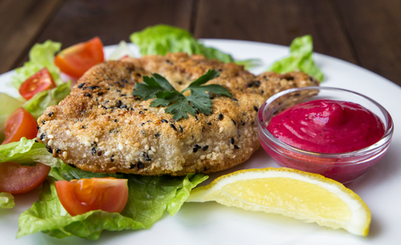 closeup of Homemade Breaded Schnitzel with salad and berry sauce on old wooden table Stock Photo
