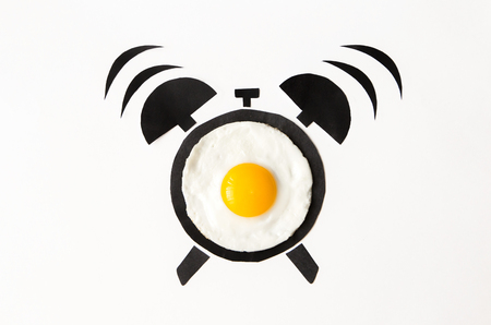Fried egg in shape of alarm clock, breakfast time concept. top view