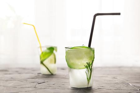 twee glazen met verse cocktail gemaakt van ijs op betonnen tafel voor raam. concept Stockfoto