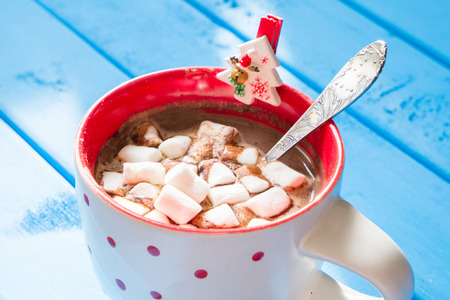 closeup of Christmas hot chocolate with marshmellow on blue wooden background.