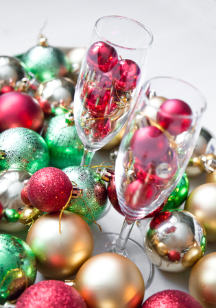 closeup of Christmas balls in wineglass on a bright abstract background. vertical