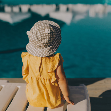 Little girl in yellow dress and hat sits back by the pool with blue water.