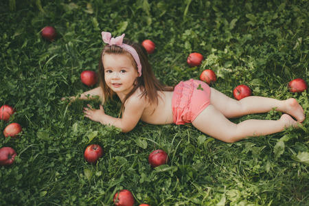 A child with long hair lying on the grass with red apples. The girl is wearing pink panties and a bow. Sunny and warm. 免版税图像