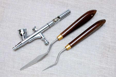 Aerógrafo y paleta cuchillo sobre lienzo gris  Foto de archivo