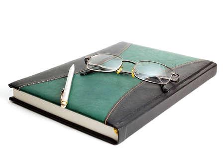 Libro y anteojos sobre fondo blanco