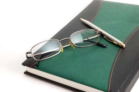 Libro y gafas sobre fondo blanco Foto de archivo