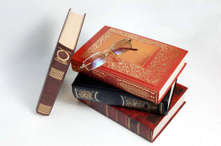 Books and eye glasses on white background photo