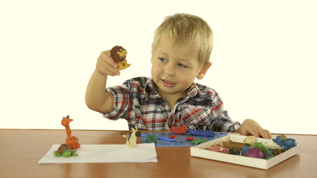 child's play clay: little boy sculpts from plasticine animals