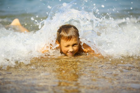 15 18: kid in the foam of waves Stock Photo