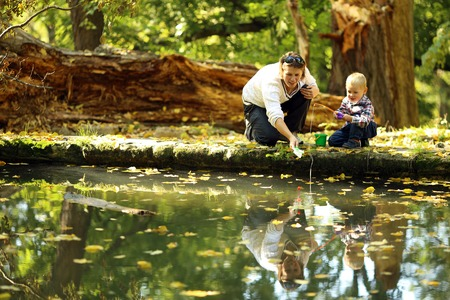 boy with his mother catches a fish in the autumn park photo