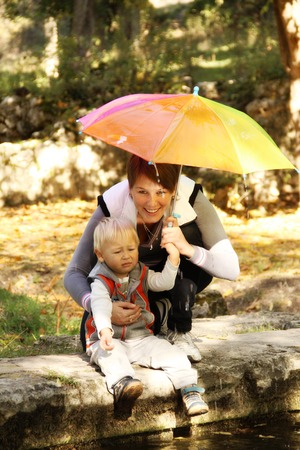 Mother with baby in the park under an umbrella photo