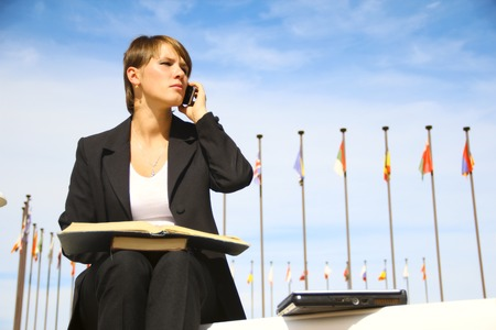 file clerk: business woman working on a background of international flags