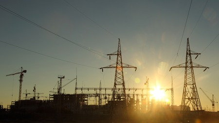 power lines: silhouettes of construction and power lines at sunset