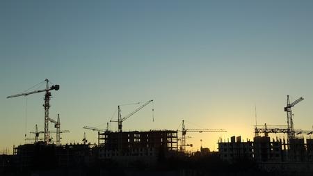 日没時の建設および電力線のシルエット