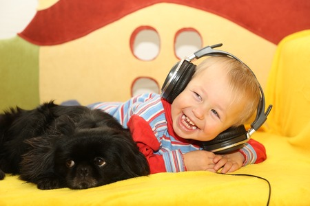 funny kid with a dog listening to music in headphones Stock Photo