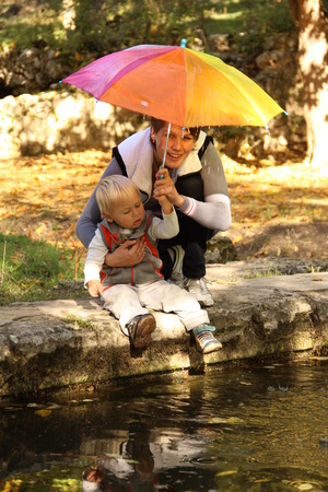 mom with a little boy under an umbrella in the rain photo