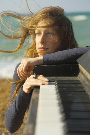 old piano: beautiful  girl from an old piano on the coast