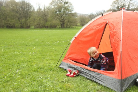 15 18: funny kid playing in a tent on the nature