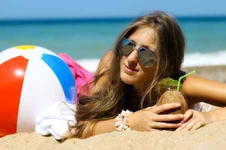 girl with an exotic cocktail posing on the sandy beach photo
