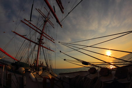 tripping: sunset on the sea with an old sailing ship