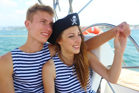 pirate crew: couple in love pirates at the helm of a yacht cruise