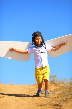 flight helmet: kid with wings and flying helmet plays in the pilot in the plane