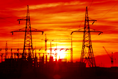 electricity substation: Background - power lines going to the construction site at sunset Stock Photo