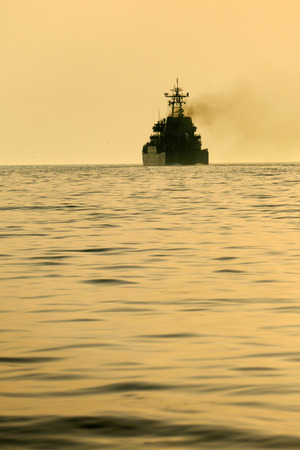 warship: silhouette of a warship at sea on a sunset background