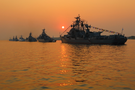 silhouette of military ships on a background sunset
