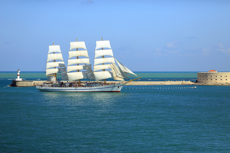 Beautiful old sailboat on the background of the sea fort
