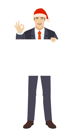 Businessman in Santa hat holding white blank poster and showing a okay hand sign.