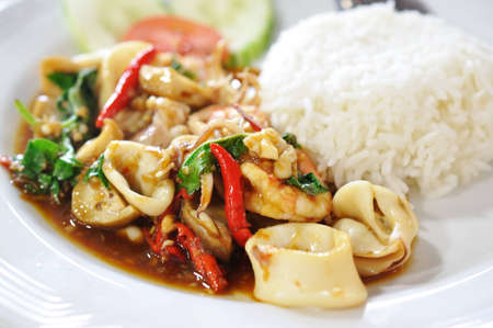 rice topped with stir fried hot and spicy seafood with basil Stock Photo