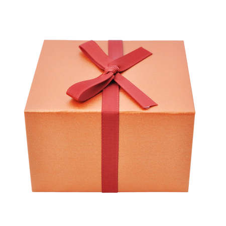 Single gold gift box with red ribbon on white background.  Stock Photo