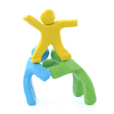 team work three colorful plasticine guys making a human pyramid
