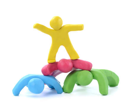 team work four colorful plasticine guys making a human pyramid Stock Photo