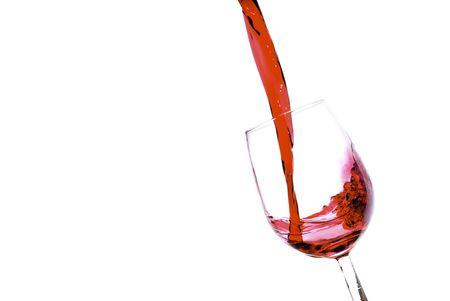 Versando il vino rosso in un bicchiere inclinato