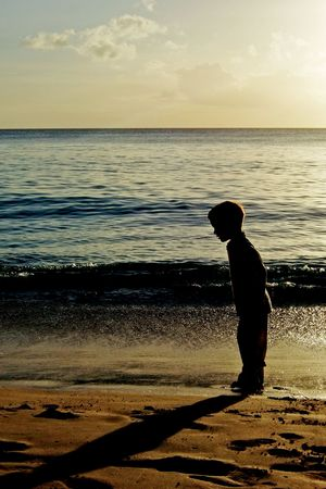 Silhouette of a boy looking at his shadow during a sunset on a beach photo