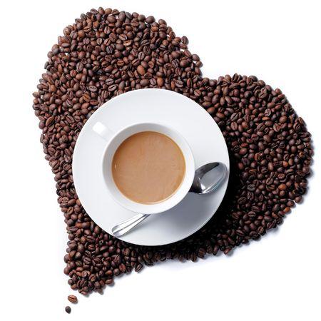 Vista superiore tazza di caff� a forma di cuore con chicchi di caff� in background