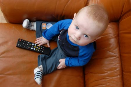 Little baby boy playing with TV remote photo