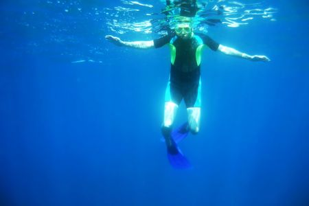 L'uomo cerca in mare blu profondo, mentre lo snorkeling