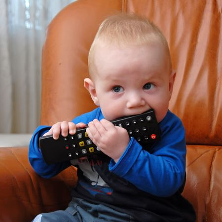 Adorable baby boy chewing the TV remote control Stock Photo