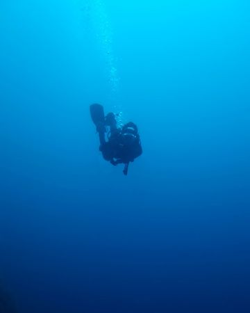 Blue water: Silhouette of a diver going deep into the blue ocean Stock Photo