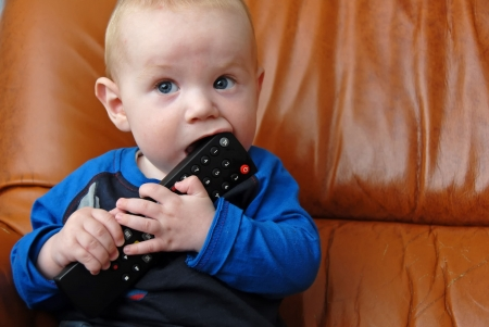 Adorable baby boy chewing a tv remote